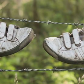 this is an image of an old pair of trainers hanging on a wire fence